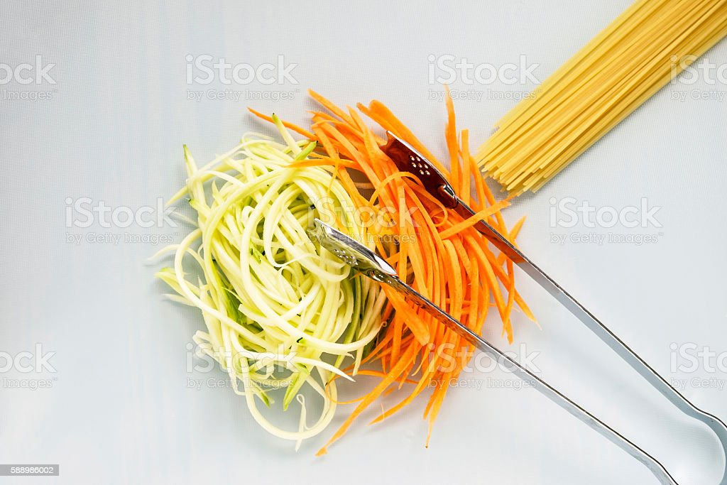 Zucchini and carrot with spaghetti on white chopping board stock photo