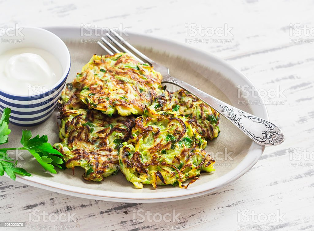 Zucchini fritters with herbs on a ceramic plate stock photo