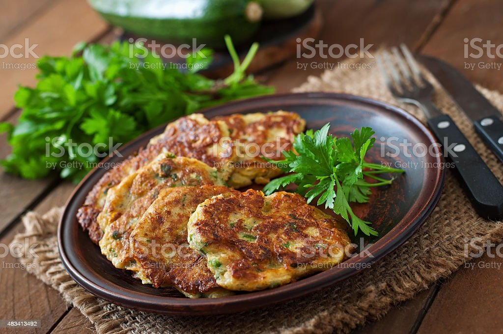 Zucchini pancakes with parsley on a wooden table. stock photo