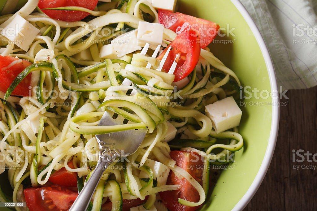 zucchini pasta with feta and tomatoes macro. horizontal top view stock photo