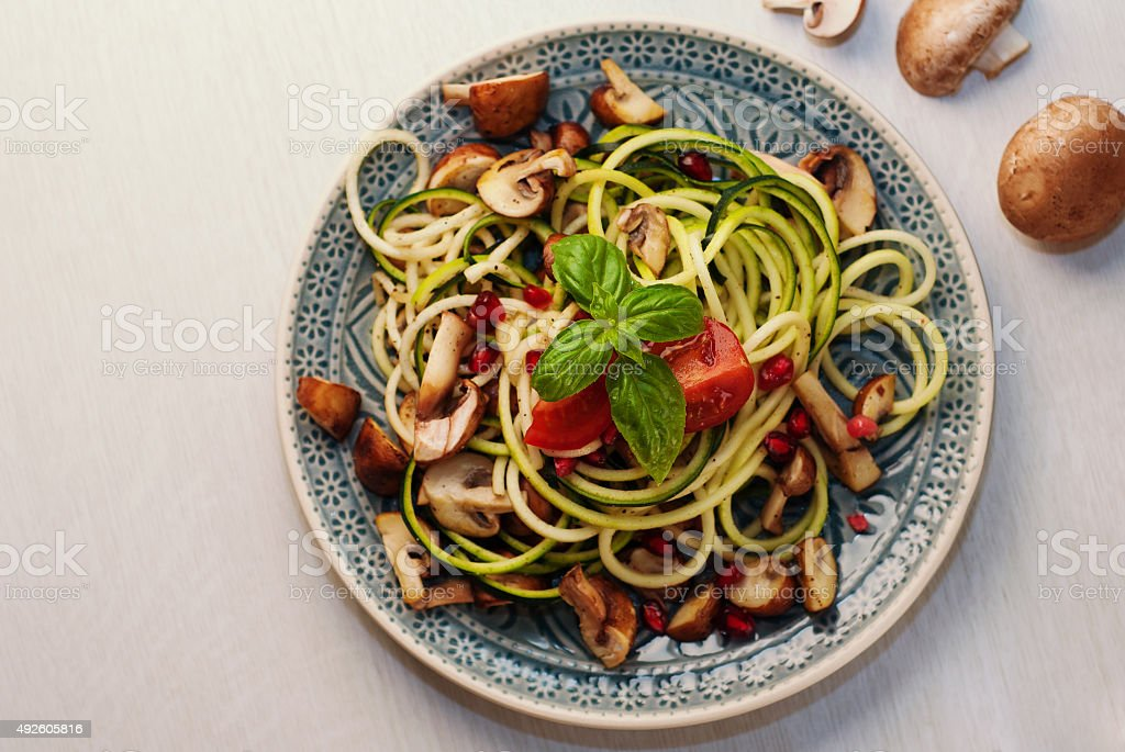 Zucchini pasta/noodles with mushrooms and pomegranate seeds stock photo
