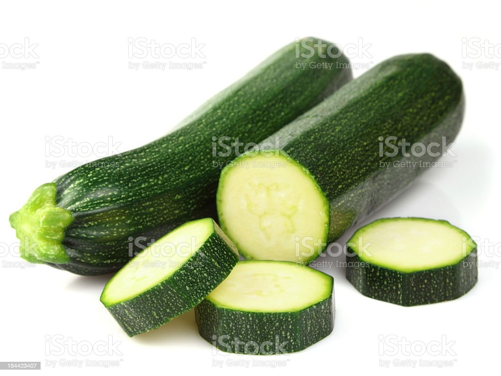Zucchini, whole and partially sliced, on white background stock photo