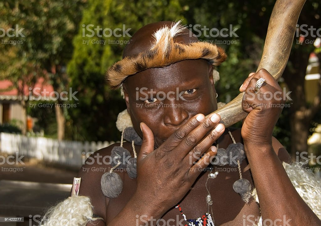 Zulu African man blowing a horn royalty-free stock photo