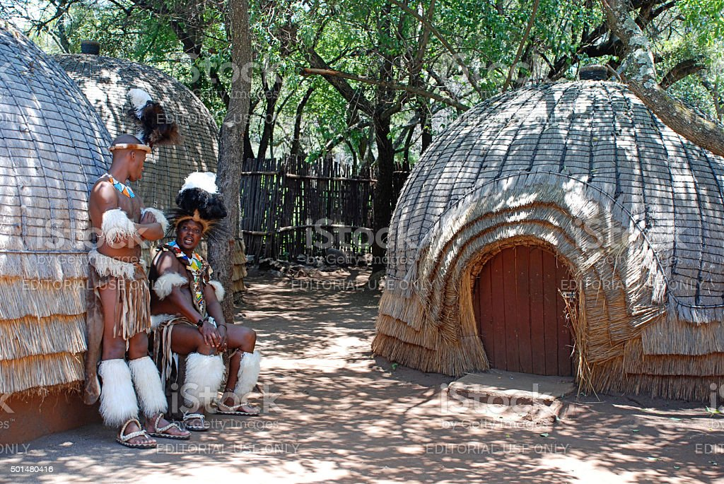 Zulu men near tribal straw house, South Africa stock photo