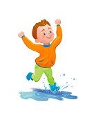 Boy in raincoat jumping and playing in the rain