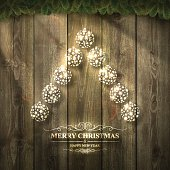 Bright Christmas tree with baubles on wooden background