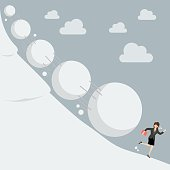 Business woman running away from snowball effect