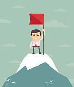 Businessman with flag on a Mountain peak.