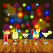 Cocktails on wooden table and bar lights background