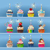 Collection of festive cupcakes with sparklers and candles.