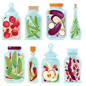 Different glass jars with preserved vegetables and fruit.