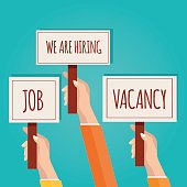 Hands holding signboard with We are hiring