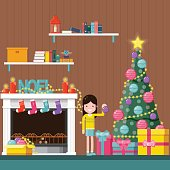 Happy girl decorating the Christmas tree near a fireplace at