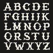 Old serif alphabet font on the dark background.