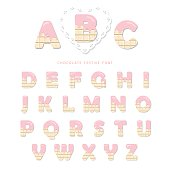Pink cream melted on white chocolate decorative alphabet. Cute letters