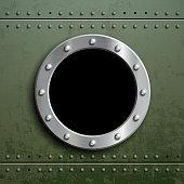 Round window porthole on green metal background.