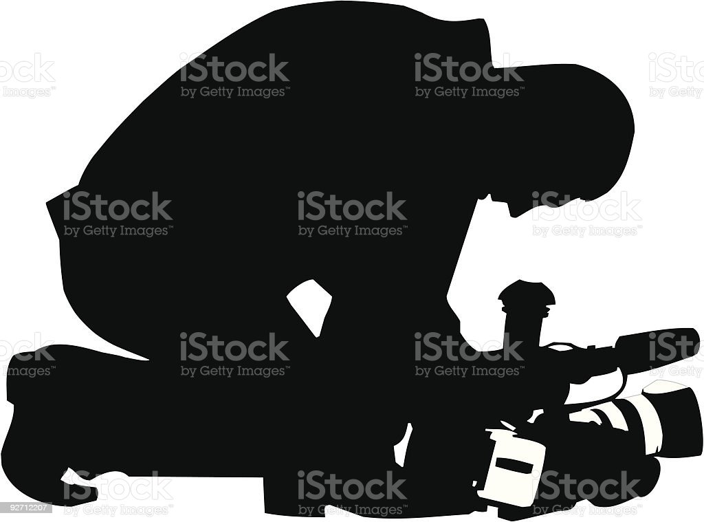 Silhouette of a camera man kneeling down with his camera royalty-free stock vector art
