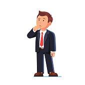 Standing business man making thinking gesture