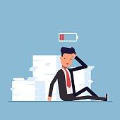 Tired businessman or manager sitting near the pile of documents