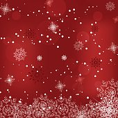 Vector holiday abstract red background with snowfall, radiance and snowflakes.