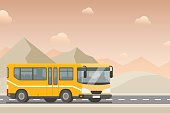 Yellow bus goes on the highway in the desert.