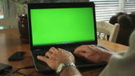 MAN TYPES ON A LAPTOP WITH GREENSCREEN video