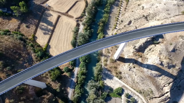 1080p Aerial, Flight over a highway bridge and down river village and olive orchards, Andalucia, Spain. Staright rows of olive trees and high rise bridge with going on cars. Way to Cordoba video