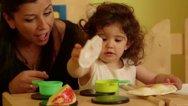 3of15 Little child, girl, woman, teacher playing in kindergarten, school video