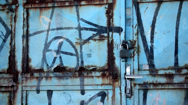 3rd world urban decay. Locked door filled with graffiti and urban decay video