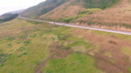 4k aerial view big sur from hills to highway car follow highway commercial video