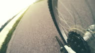 4k bicycle rear wheel footage: a bicyclist rides further along the asphalted road video