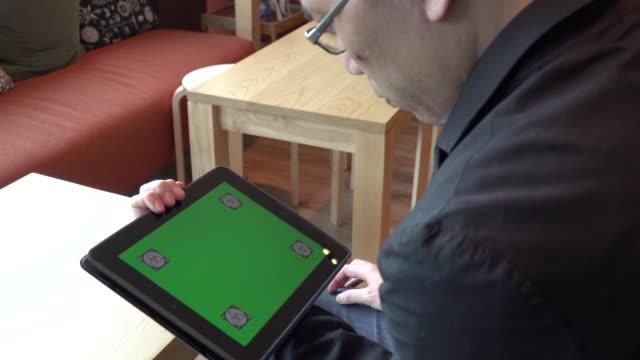 4k: business man over shoulder shot of using tablet green screen video