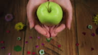 4k Colourful Composition of Fresh Apple in Hand - Wooden Background video