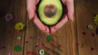 4k Colourful Composition of Fresh Avocado in Hand - Wooden Background video