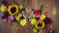 4k Colourful Composition of Fresh Flowers Heart - Wooden Background video