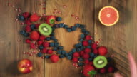 4k Colourful Composition of Fresh Fruits Heart Shaped- Wooden Background video