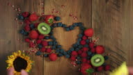 4k Colourful Composition of Fresh Fruits- Heart with flowers, Wooden Background video