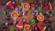 4k Colourful Composition of Fresh Fruits Juice and Ice - Wooden Background video