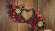 4k Colourful Composition of Fresh Fruits taking one berry - Wooden Background video