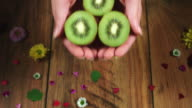 4k Colourful Composition of Fresh Kiwi in Hand - Wooden Background video