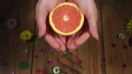 4k Colourful Composition of Fresh Orange/Grapefruit in Hand - Wooden Background video