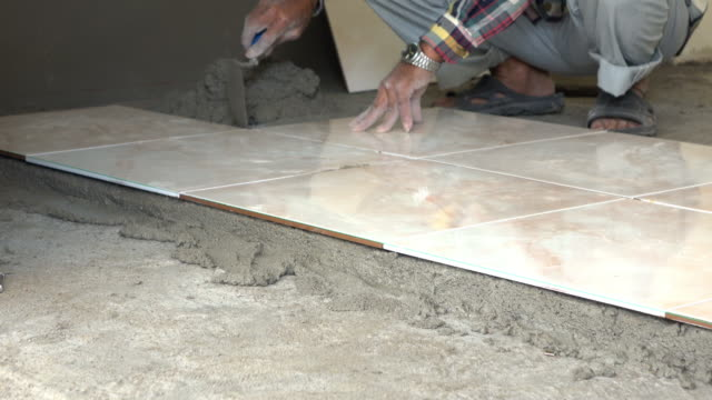4k, construction worker tiling ceramic tiles floor using putty knife video