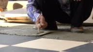 4k, construction worker tiling ceramic tiles floor using putty knife video