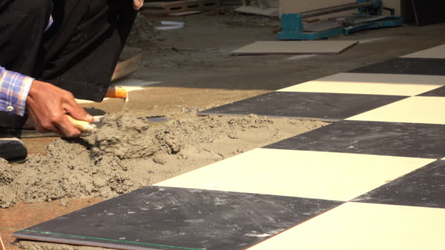 4k, construction worker using putty knife tiling floor video