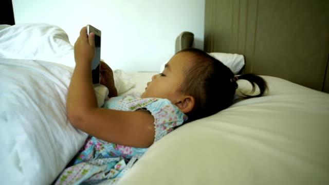 4k dolly: kids playing games using the phone on the bed video