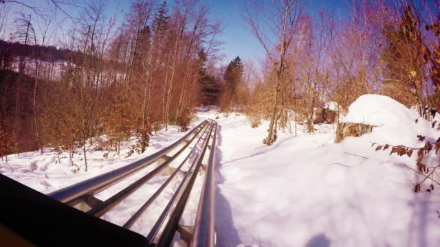 4k exciting multi-views footage: father and son enjoy bobsleighing on their winter vacation video