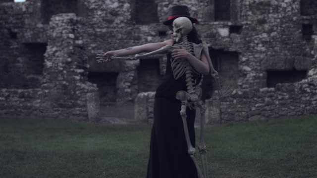 4k Halloween Shot of a Witch Dancing with a Skeleton video