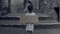 4k Horror Shot of an Abandoned Child Holding 'Help' on cardboard video