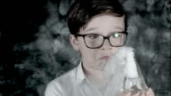 4k Science Shot of a Boy in Laboratory Holding Toxic Liquid with Smoke video