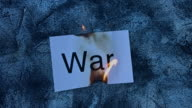 4k shoot of a creative composition with war word on fire video
